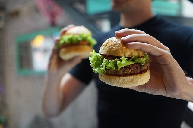 Guy holding two hamburgers